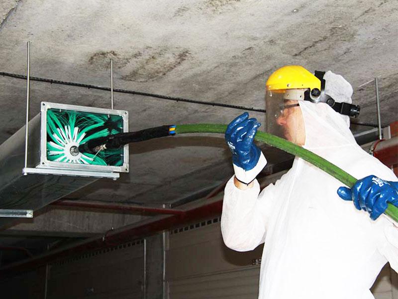 Процесс очистки вентиляционного канала специалистом